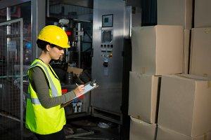 Female worker writing on clipboard in warehouse