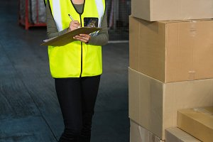 Female worker noting on clipboard in warehouse