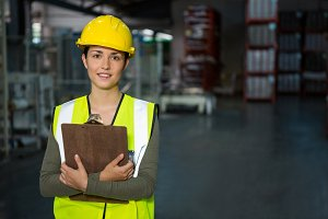 Confident female worker holding clipboard in warehouse