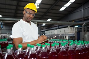 Male worker noting about products in warehouse