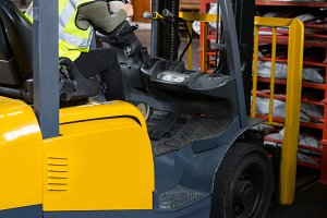 Female worker driving forklift in factory