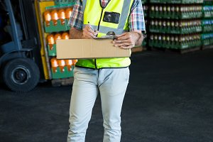 confident male worker writing on clipboard in warehouse
