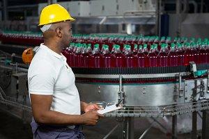 Male worker inspecting bottles in juice factory
