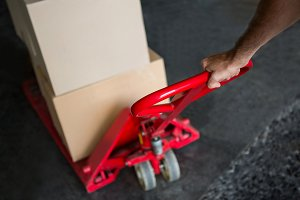 Cropped hand of worker pulling trolley in warehouse
