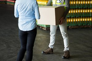 Manager looking at male worker working at warehouse