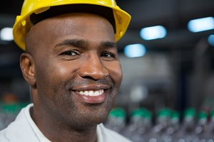 Portrait of smiling male worker wearing hard hat in warehouse