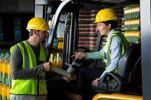 Male worker showing clipboard to female worker
