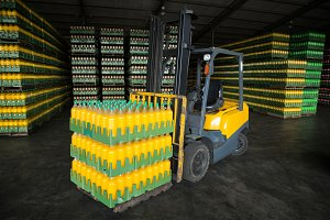 Stack of packed juice bottles and forklift