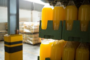 Yellow juice bottles in crate at warehouse