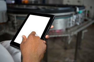 Mid section of male worker using digital tablet