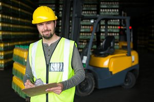 Smiling male worker writing on clipboard in warehouse