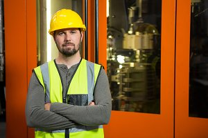 Confident male worker standing against door at factory