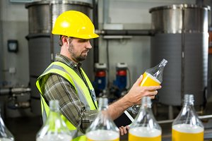 Serious male worker inspecting bottles in juice factory