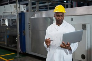 Male worker using laptop in manufacturing industry