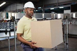 Male employee carrying cardboard box in juice factory
