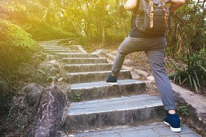 Man hiking in the forest as he climbs on the stair - travel and hiking