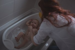 Mother bathing baby in bathtub