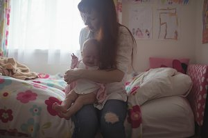 Mother with crying baby sitting on bed