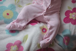 Low section of baby lying in bed