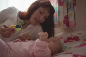 Loving mother playing with baby in bed