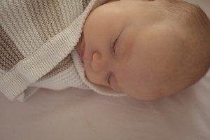 Close-up of cute baby sleeping in crib