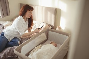Mother taking picture of baby sleeping in crib