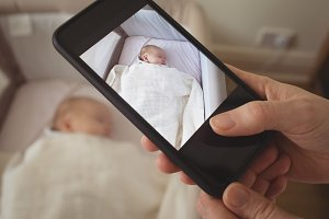Mother taking picture of sleeping baby through mobile phone
