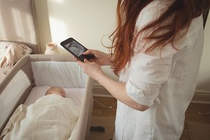 Mother taking picture of sleeping baby in crib