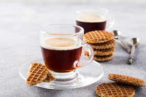 Glass cup of coffee with syrupwaffles cookies