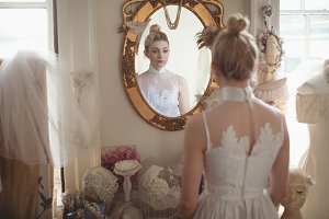 Young bride in a white dress looking into mirror