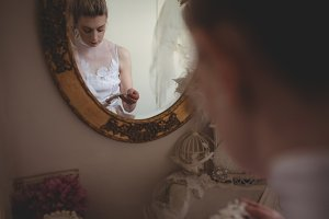 Young bride in a white dress choosing laces