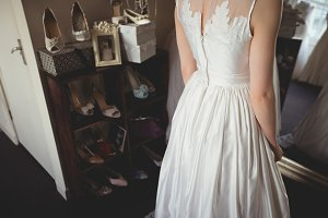 Mid-section of young bride in white wedding dress