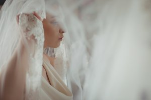 Young bride in a white dress wearing veil