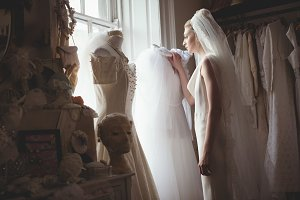 Young bride in a white dress looking through the window