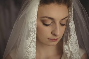 Young bride in a white dress looking away