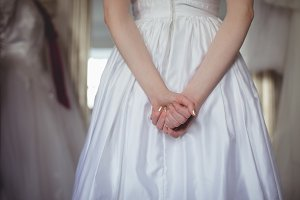Bride in white dress holding hands behind her back