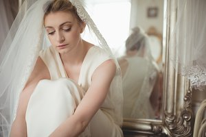 Thoughtful young bride in a white dress relaxing