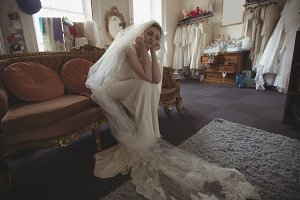 Thoughtful young bride in a white dress sitting on sofa