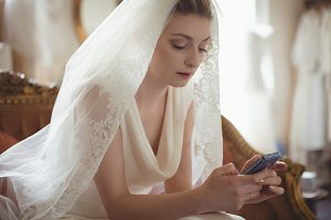 Young bride using mobile phone on sofa