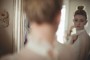 Young bride looking at herself in mirror