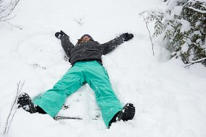 Woman doing snow angel on beautiful snowy day
