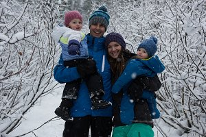 Cheerful family amidst snow covered bare trees