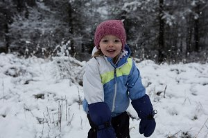 Cheerful girl wearing warm clothing in snow