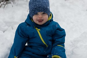 Portrait of cute boy sitting on snow covered land