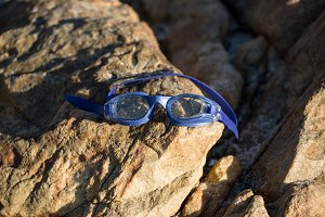 Swimming goggles on rock
