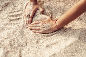 Woman hands holding sand on the beach