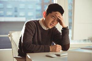 Depressed male executive sitting at desk