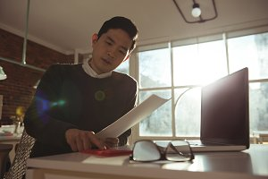Male executive using calculator at desk