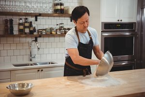 Chef emptying flour on counter top at restaurant