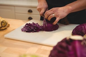 Chef cutting red cabbage in commercial kitchen